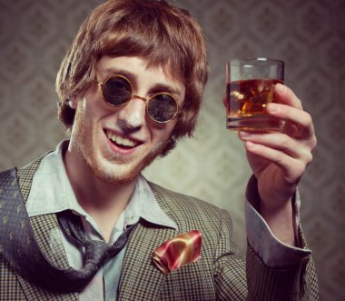 Guy holding a glass of whisky
