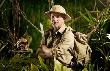 Adventurer with colonial style survival equipment in the jungle with skull.