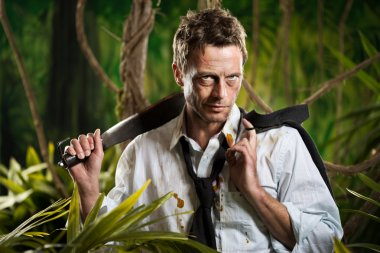 Businessman with machete walking in the jungle