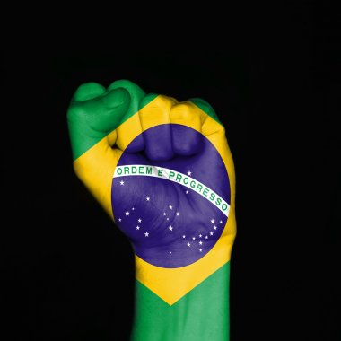 Brazil flag on fist over black background. Symbol of strength.