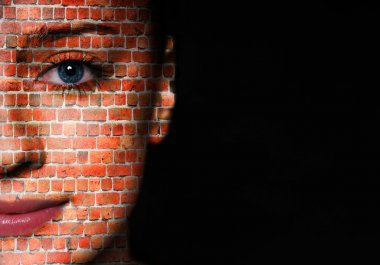 Woman face covered with brick wall pattern over black background