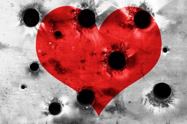 Red heart shape on metal plate with bullet holes