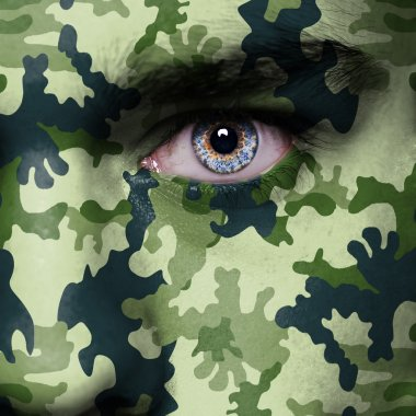 Woodland camouflage painted on woman a face - army concept