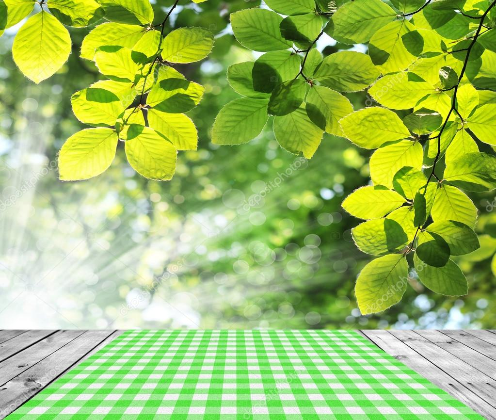 Empty table with green leaves background.