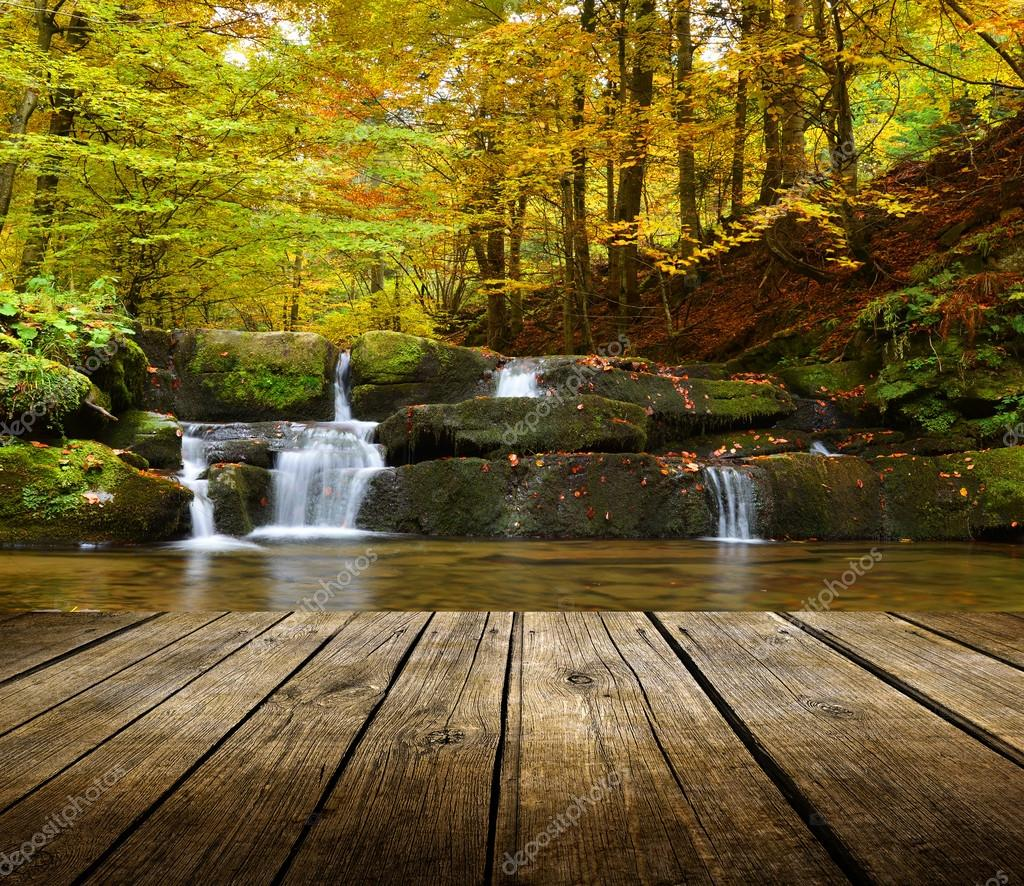 Autumn waterfall background with empty table