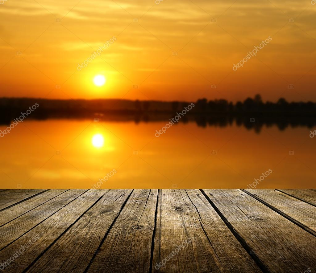Empty wooden deck table with sunset in background