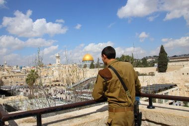 Israeli soldier looking at the wailing wall