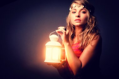 beautiful girl with lantern seeking in night. Vintage retouching