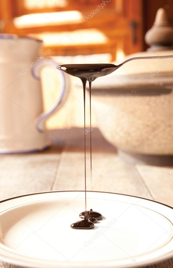 Blackstrap molasses drizzling from a teaspoon