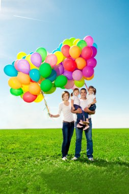 Happy family holding colorful balloons. Mom, ded and two daughte