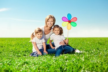 Happy family together in outdoor park at sunny day. Mom two dau