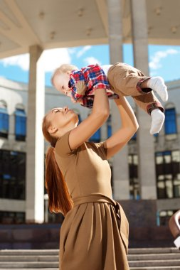 Fashionable modern mother on a urban street with a pram. Young m