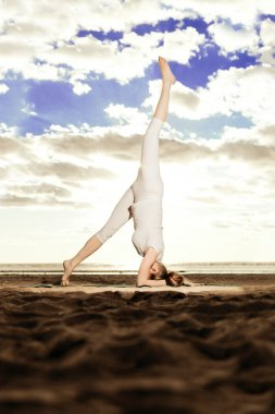Young beautiful slim woman practices yoga on the beach at sunris