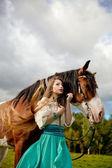 Fotografie schöne Frau mit einem Pferd im Feld. Mädchen auf einer Farm mit einem