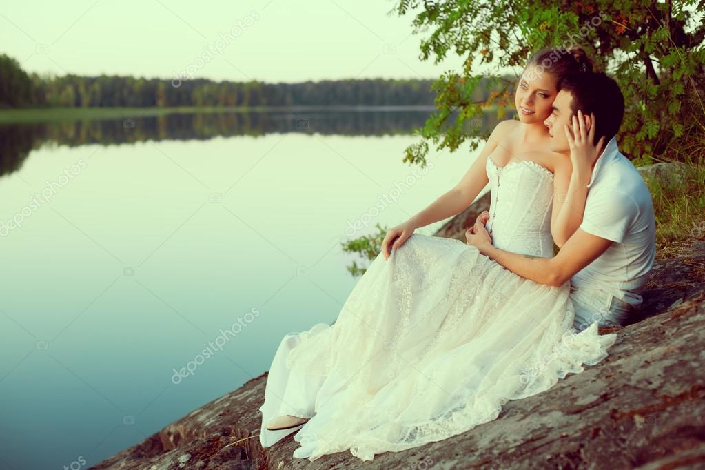 Loving couple hugging on the lake. Beauty young woman and man in