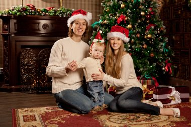 Happy smiling family near the Christmas tree celebrate New Year.