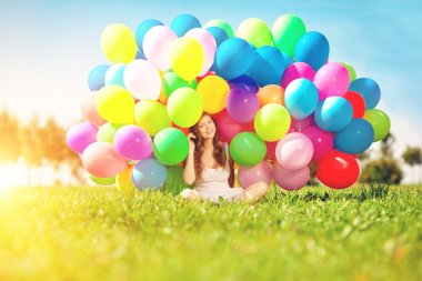 Happy birthday woman against the sky with rainbow-colored air balloons in her hands. sunny and positive energy of nature. Young beautiful girl on the grass in the park. stock vector