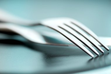 Artistic cutlery fork and knife macro on plate
