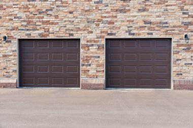 Two garage doors on brick wall.