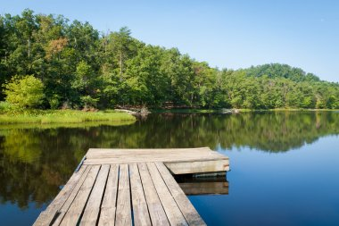 Summer view of a small country lake with wooden pier.