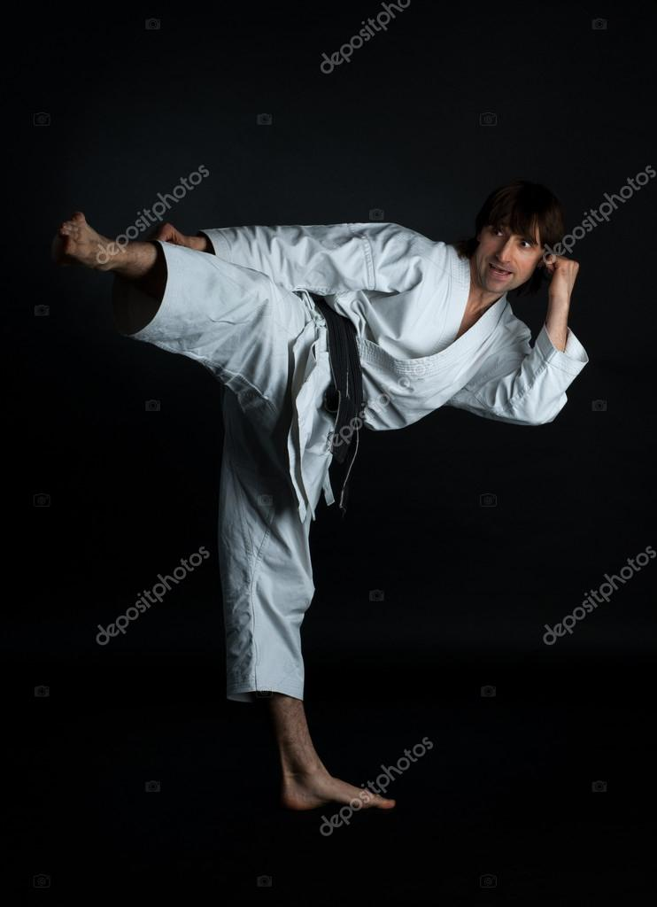 Man doing karate kick with your foot on a black background