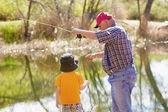 Fotografie kleinen Jungen und seinem Großvater einen Fisch fangen