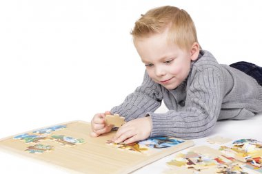 Young boy solving a puzzle