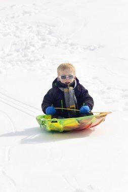 Young Boy snow sledding down a hill stock vector