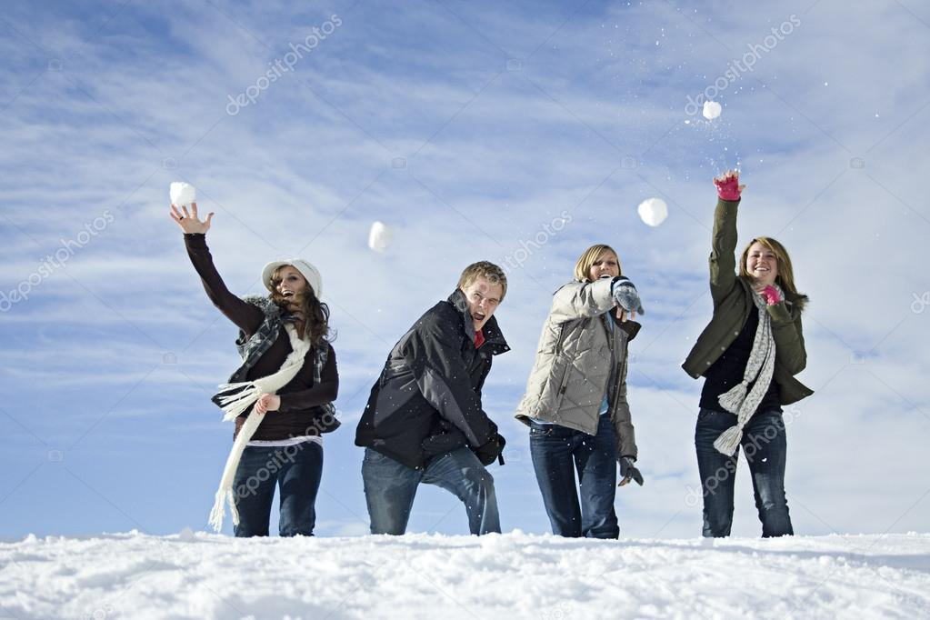 Young adults snowball fighting