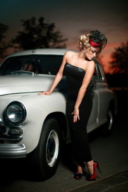 Beautiful sexy woman standing near old car in retro style