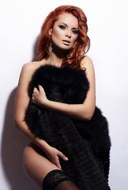 Sexy redhead stylish model in lingerie in fur coat