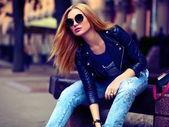 Fotografia Ritratto di carino divertente moderno sexy giovane elegante sorridente donna ragazza modello urbano in panno moderno luminoso seduto allaperto nel parco in jeans su una panchina in occhiali
