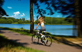 Rücken der sexy heißen Sport blonde Frau Modell auf dem Fahrrad im grünen Sommerpark in der Nähe des Sees mit fliegenden erhöhten Haaren in der Luft