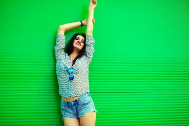 Portrait of cute funny sexy young stylish smiling woman girl model in bright modern cloth in jeans shorts with pink lips perfect sunbathed body outdoors in the city near green wall