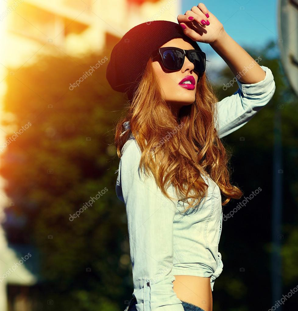 High fashion look.glamor lifestyle blond woman girl model in casual jeans shorts cloth outdoors in the street in black cap