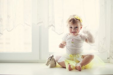 Smiling baby girl sitting near the window