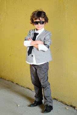 Portrait of little stylish boy outdoors in a suit