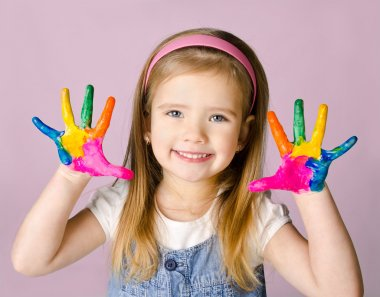 Smiling little girl with hands in the paint