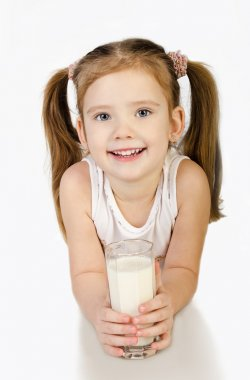 Cute smiling little girl is drinking milk isolated