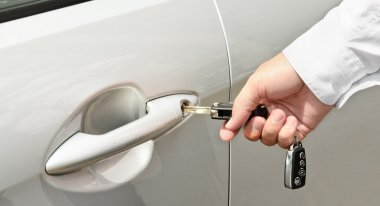 Man's hand inserting a key into the door lock of a car