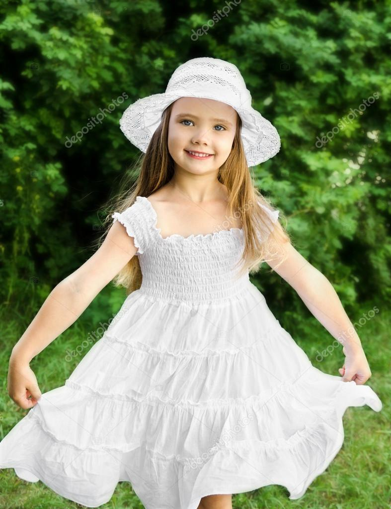 257607122 Outdoor portrait of adorable smiling little girl in white dress and hat —  Photo by ...