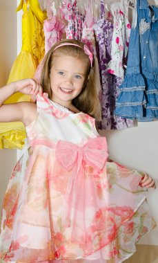 Cute smiling little girl chooses a dress from the wardrobe