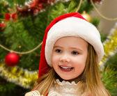 Fényképek aranyos kis lány a karácsonyfa közelében santa kalap