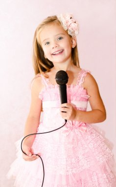 Beautiful little girl with microphone in princess dress