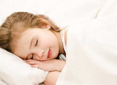 Little girl sleeping in the bed