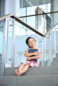 Fotografie junges Mädchen auf der Treppe zu lesen