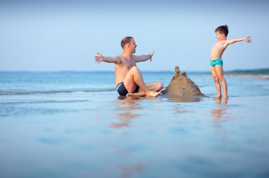 Young father and his son having fun at beach