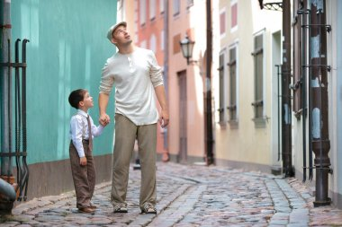 Father and son walking outdoors in city