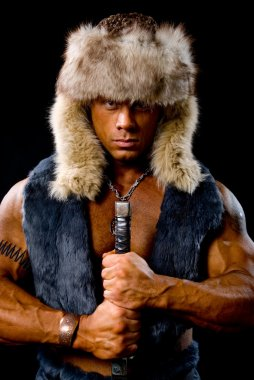 Muscular man warrior with a sword in a fur hat