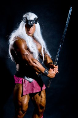 Muscular man in an image of a barbarian with a raised sword.